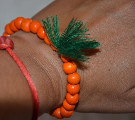 Oranžový náramok so strapcom,